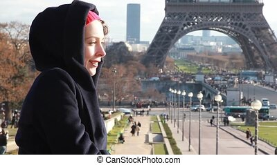 woman stands against Eiffel Tower in Paris, France - smiling...