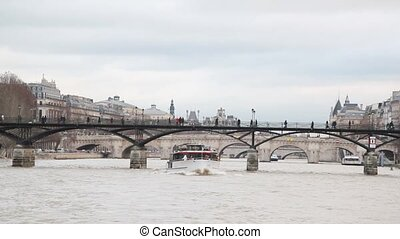 view from cutter moving in Siene river past by bridge Pont des Arts, Paris, France