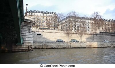 view from cutter moving under bridge over Siene river in evening Paris
