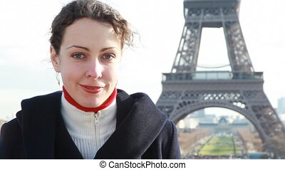 woman stands against Eiffel Tower in Paris, France -...