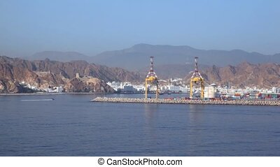 view from ship moving pass by seaport of Muscat, Oman