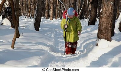 little girl  walks with ski stick in winter wood