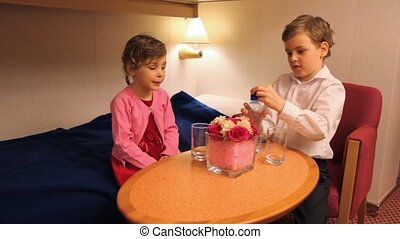 boy and girl sits at table - boy and little girl sits at...