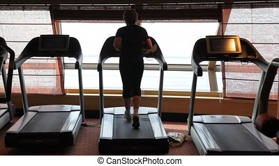 unidentified woman workout on treadmill running in gym of...