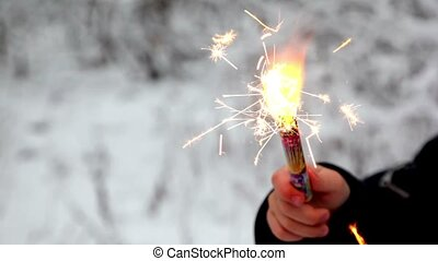 Firework fire in children's hand in snow forest