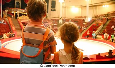 two kids stands against arena in circus after performance -...