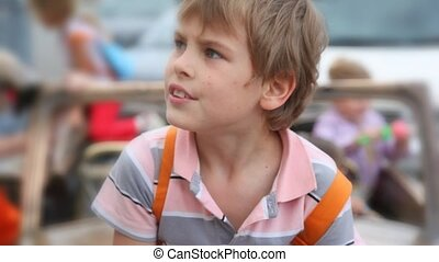 outdoors portrait of boy, other kids plays in background