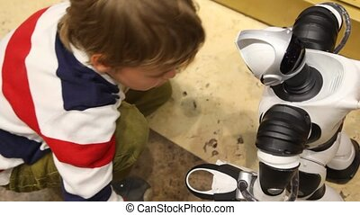 boy plays with radiocontrol toy robot in shop and holds his...
