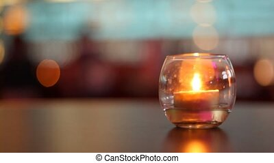 Candle lit inside glass which stands on table in some bar
