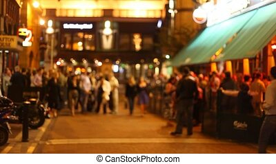 Out of focus view on people walking on a street