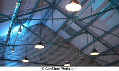 Colour projectors lighting the concrete roof and bars on...