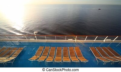 row of deckchairs on deck of cruise ship in sea and small...