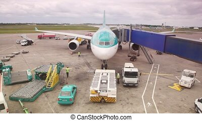 airplane standing at airstrip is serviced by airport workers...