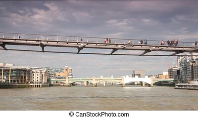 People walking across River Thames on London Millennium...