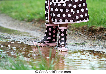 Rainboots and Mud Puddles - Childs feet playing in a mud...