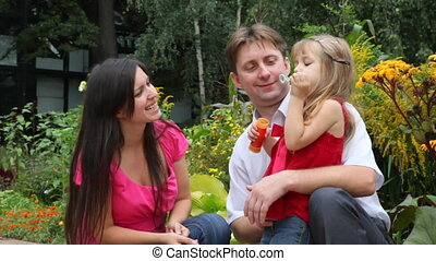 family blowing soap bubbles - Happy family with one little...