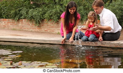 family playing with water near pound - Happy family with one...