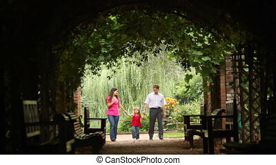 family walks in plant tunnel with bends