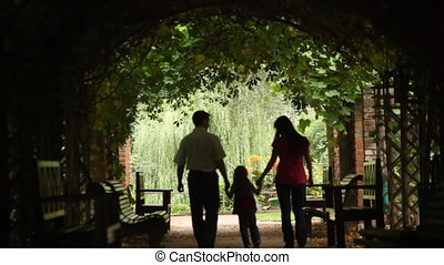 silhouettes of parents with kid who walks in plant tunnel