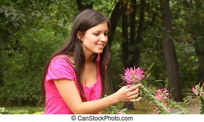Good looking woman smell some flower in park - Good looking...
