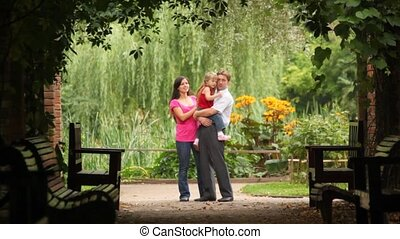 Family carrying one kid hugging embracing and kissing her