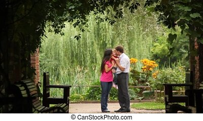 Family carrying one child hugging embracing and kissing in the plant tunnel