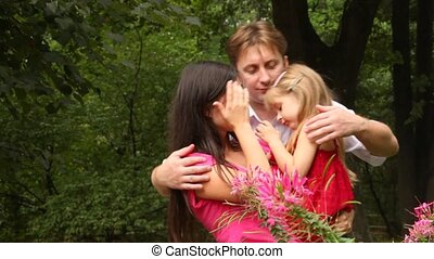 Family carrying one child hugging embracing and kissing -...
