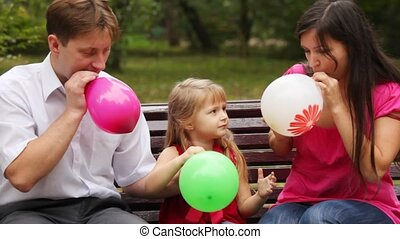 family blow balloons sitting on bench in park