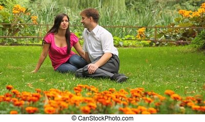 couple sitting in park amid flowers - Happy couple sitting...
