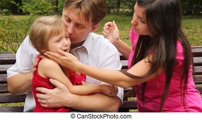 couple embraces their crying daughter and try to calm her -...