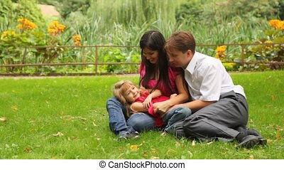 couple plays game with their daughter - Young happy couple...