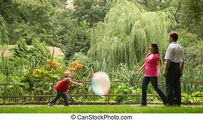couple play ball with daughter near fence in park - Young...
