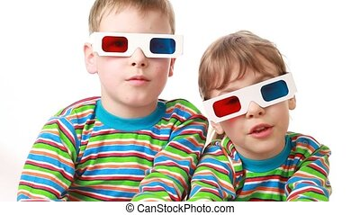 boy and girl sit in anaglyph glasses for viewing stereo images and applaud