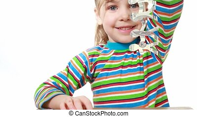 girl lifts a ribbon of paper cut manikins with image of...