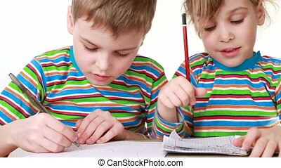 girl and boy with a chocolate-smeared mouth draw pictures in...