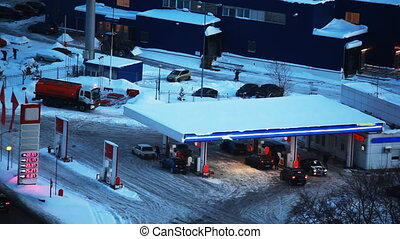 cars refuel at petrol station in winter