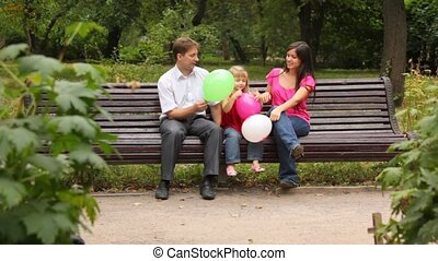 Family play game with balloons sitting on bench in park -...