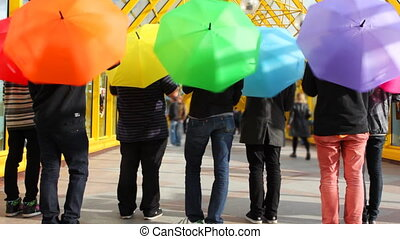 young men spin colorful umbrellas back to camera then jump up
