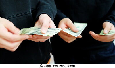 hands of two young men recount hundred dollar bills