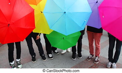 men spin colorful umbrellas and make them lower down - young...