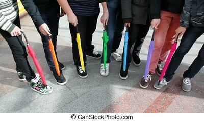 men placed folded colored umbrellas on foot and stomp -...