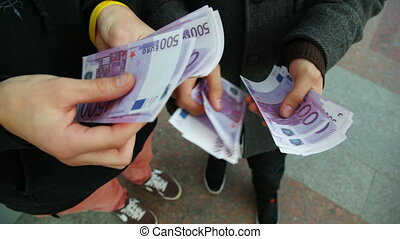 the hands of two young men recount bill for five hundred euros