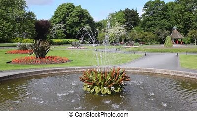 Fountain in St Stephens Green park with some people walking...