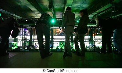 people standing on balcony inside nightclub and observing...