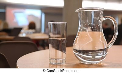 Cup and pitcher filled with water stand on table in some conference hall
