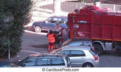 two workers lift trash bin into garbage truck at street -...