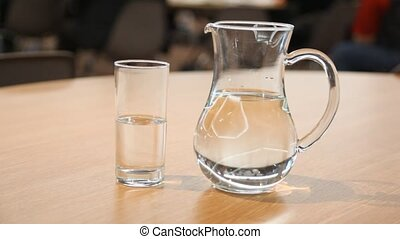 Cup and pitcher filled with water stand on table