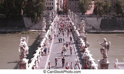 Front view on many people passing across Sant'Angelo Bridge...
