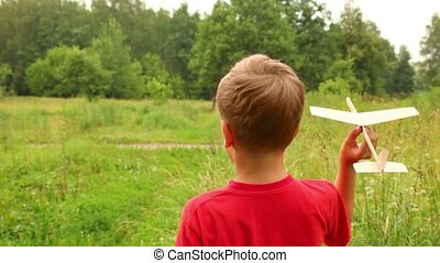 boy is flying a toy aircraft a lovely summer day