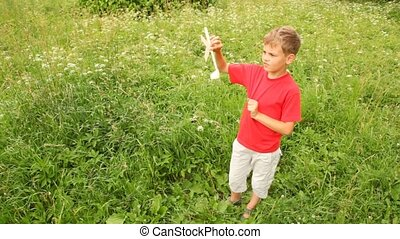 boy is playing with a model of an aircraft in the park on...